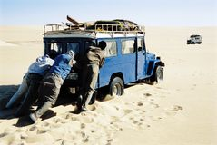 Men pushing jeep in desert Stock Photography