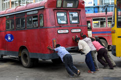 Men pushing red bus, Negombo, Sri Lanka Royalty Free Stock Photography
