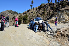 Men pushing a stranded tourist vehicle. Passerby pushing a stranded tourist vehicle in an unpaved himalayan road, Shimla, Himachal Pradesh, India, Asia Stock Image