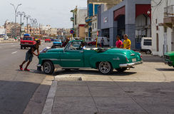 Men pushing a vintage car on Malecon in Havana. Buildings and cars on Malecon Boulevard in Havana, Cuba Stock Photography