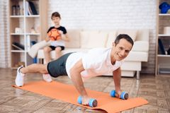 The man pushup, holding a dumbbell. The men pushup, holding a dumbbell. Next to his son. They train together at home royalty free stock photo
