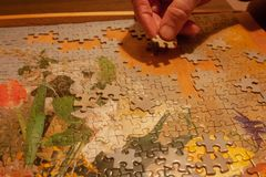A men puts a puzzle on the table. He love puzzles royalty free stock photos