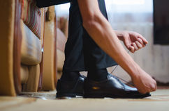 Men putting his black shoes. Hands of men getting ready in suit Stock Image