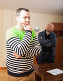 Men during  quarrel at home. Portrait of two sad men at home Royalty Free Stock Photography