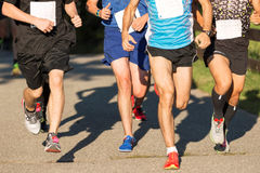 Men racing a 5K in the summer royalty free stock images