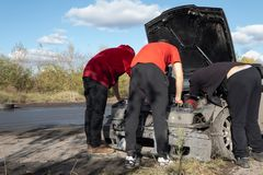 3 men repair damaged car during amateur drifting event stock photo