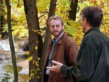 Men at ravine edge. Two men having a discussion at the edge of a ravine in autumn stock images