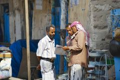 Men read newspaper at the street in Sanaa, Yemen. Royalty Free Stock Photo