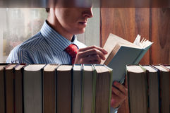 Men reading a book. Next to the bookshelf royalty free stock image