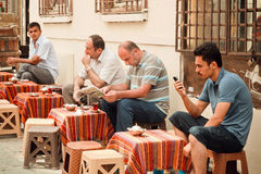 Men reading news and drinking tea in traditional outdoor cafe of turkish capital Stock Image
