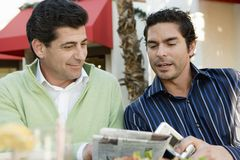 Men Reading Newspaper At Cafe. Men together reading newspaper at cafe royalty free stock image
