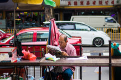 Men Reading Newspaper in a Street Market Stock Photography