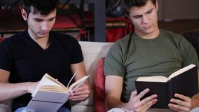 Men reading textbooks on sofa. Two casual young men posing on couch concentrated on reading books at home stock video footage