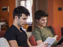 Men reading textbooks on sofa. Two casual young men posing on couch concentrated on reading books at home royalty free stock photography