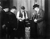 Men reading the ticker machine. (All persons depicted are no longer living and no estate exists. Supplier grants that there will be no model release issues royalty free stock photos