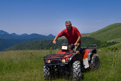 Men on a red atv in Romania quad Royalty Free Stock Images