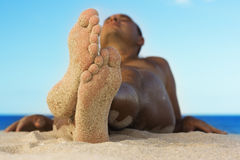 Men relaxing on the beach Stock Photography