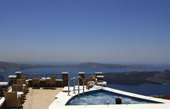 Men relaxing in a Jacuzzi. A Jacuzzi on a dream house set on a hill overlooking the sea - Santorini, Greece Stock Image