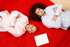 Men relaxing on rug. Two men laying side by side on their backs on a red rug in opposite directions, with their arms crossed in front of them. A blank white stock photography