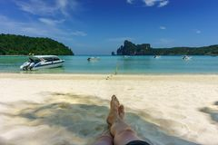 Exotic beach. male feet on a sandy beach. Men relaxing on the sandy beach in Thailand. Phi Phi Don. Vacation concept Royalty Free Stock Photo