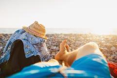 Men relaxing by sea in rocky beach Stock Photo