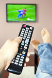 Men with the remote control. Young man watching the television, the remote control in hand Stock Photo