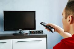Turning the TV on or off. Men with the remote control, front of the television. Young guy switches channels on the remote from the stock image