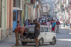 Men repairing a car in Havana, Cuba Royalty Free Stock Photos