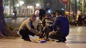 Men repairing motorbike Stock Image
