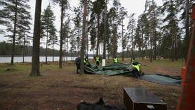 Men in rescue uniform to establish tent in forest, lake. Emercom camping. Men in rescue uniform to establish tent in forest, lake. Emercom teaching. Day stock video