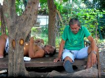 Men resting and relaxing under the shade of a tree Stock Images