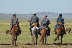 Men ride on horseback, circa Harhorin, Mongolia. Royalty Free Stock Image