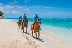 Men ride horses on the Le Morne Beach Royalty Free Stock Photography