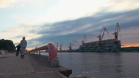 Men ride on roller skaters on seafront. Cargo port. Water. Cranes. Containers. stock footage