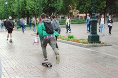 Men ride a skateboard in the Alexander Garden in the city of Moscow. royalty free stock photography