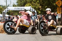 Men Riding Adult Big Wheels Race Each Other At Festival Stock Images