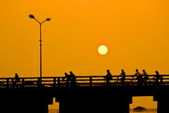 Men riding bicycles on the bridge ,sunset Stock Photos