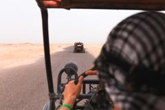 Men riding buggy car in desert Royalty Free Stock Photo