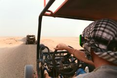 Men riding buggy car in desert Royalty Free Stock Image