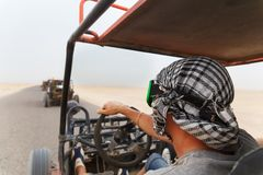 Men riding buggy car in desert Stock Photography
