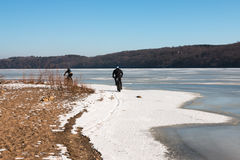 Men riding fat-bikes along frozen Mississippi River Stock Photography