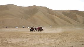 Men riding horses in an open field. A hand held, panning, wide shot of men riding horses in an open field, surrounded by sand hills stock video footage