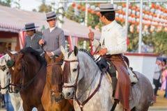 Men riding horses on Seville feria. SEVILLE, SPAIN - APR, 25: men dressed in traditional costumes riding horses on feria de abril on April, 25, 2014 in Seville Royalty Free Stock Photo