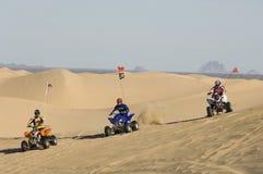 Men Riding Quad Bikes In Desert. Three men riding quad bikes in desert Stock Photos