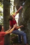 A man rock climber climbing a rock and his partner insuring. royalty free stock images
