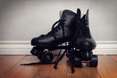 Men roller skates on hardwood floor. With grey wall Royalty Free Stock Photography
