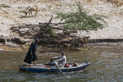 Men rowing down the River Nile near Luxor in Egypt. Men rowing a boat close to the bank of the River Nile near Luxor in Egypt Stock Photo