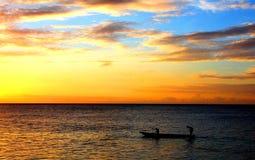 Men rowing a dugout canoe at sunset Stock Photos