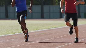 Men running around stadium doing morning exercises, competition, slow-motion. Stock footage stock footage