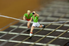 Men running down the arm of a guitar Stock Photography